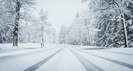 A wide shot of a road fully covered by snow with pine trees on both sides and car traces